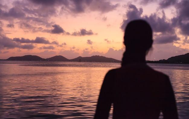 Femme se sentant rafraîchie avec panorama du coucher de soleil romantique ciel et mer en soirée avec reflet de la lumière dorée sur l'eau.