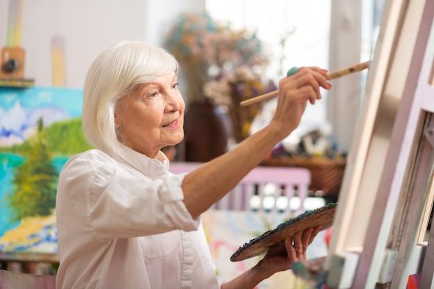 Femme se sentant soulagée. joyeuse femme aux cheveux blonds se sentant soulagée tout en peignant en atelier