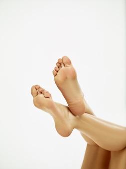 La femme se soucie de ses pieds. jeune femme musclée ou athlète féminine au studio isolé sur fond blanc. fit modèle caucasien avec un corps parfait. fitness, sport, beauté, concept de peau fraîche.