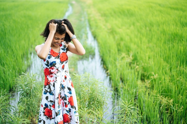 La femme se tenait tendue et la main tenait ses cheveux dans le pré