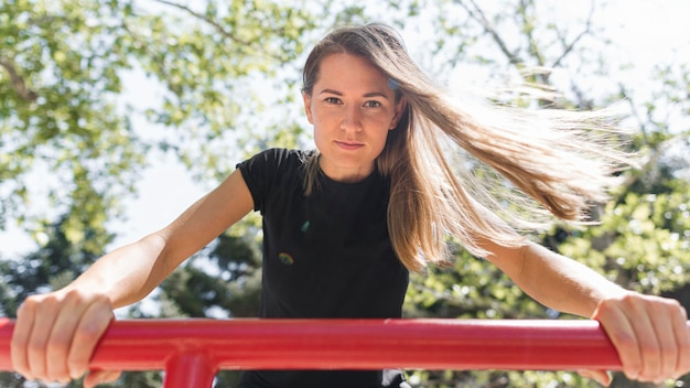 Femme se tenant sur une barre de métal rouge