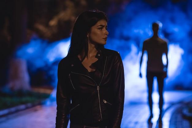La femme se tient dans une rue sombre sur fond d'homme en fumée. la nuit