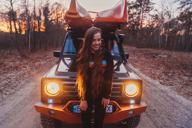 Femme se tient devant un véhicule tout-terrain 4x4