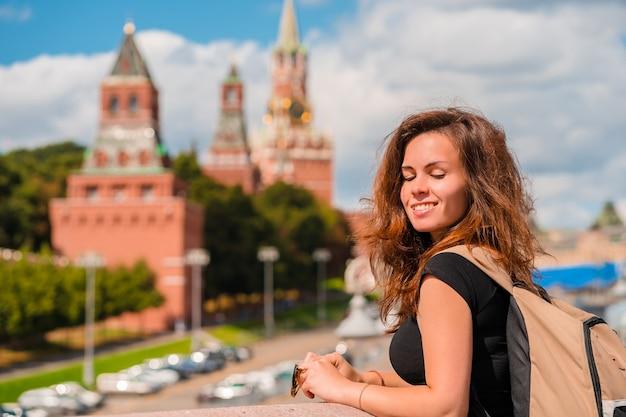 Une femme se tient sur un pont avec un espace sur le kremlin à moscou, la principale attraction de la russie