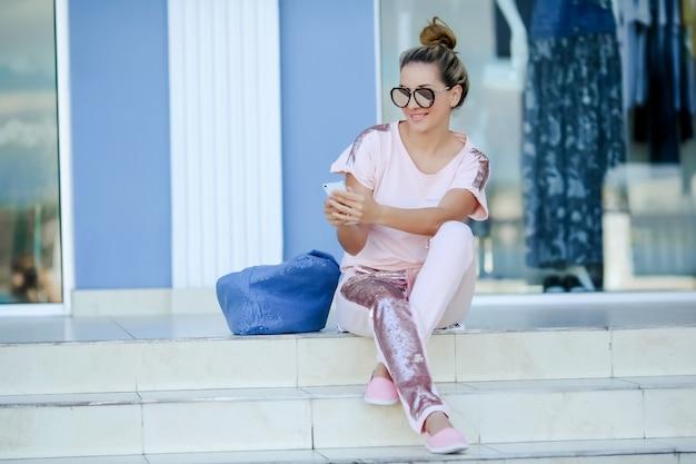 Une femme se tient près du centre d'affaires et écrit un message texte sur un téléphone mobile
