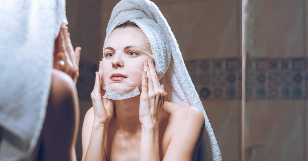Femme se tient près d'un miroir avec une serviette sur la tête et met un masque cosmétique