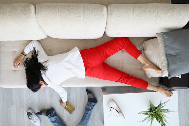 Femme se trouve sur le canapé et tient une bouteille d'alcool dans sa main