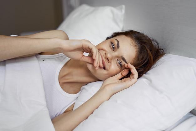 Femme se trouve dans l'intérieur de confort de repos de lit de matin