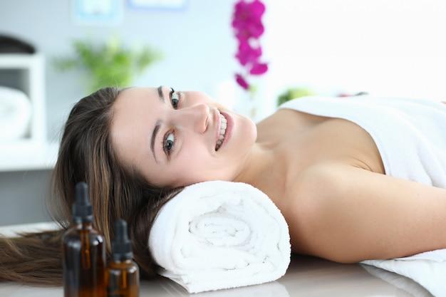 La femme se trouve dans une salle de massage et sourit
