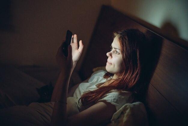 La femme se trouve hors du lit la nuit avec un téléphone dans ses mains reste salle virtuelle.