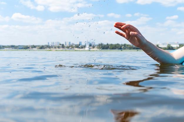 Une femme se trouve sur un paddle board sur la rivière et pulvérise de l'eau avec sa main