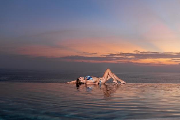 Femme se trouve et se détend au bord de la piscine à débordement au coucher du soleil