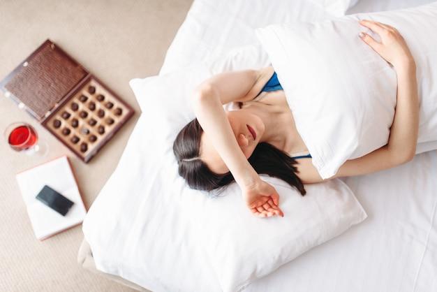 Femme se trouve sous la couverture, vue de dessus, dépression