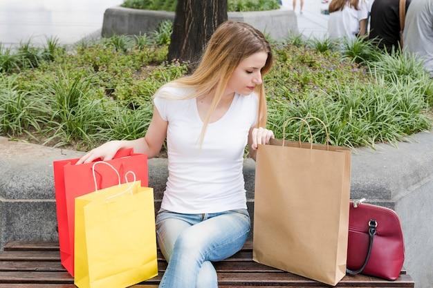 Femme, séance banc, regarder, intérieur, sac shopping