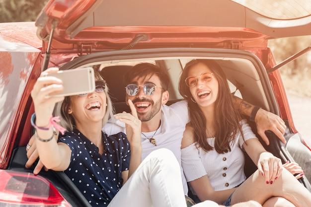 Femme, séance, coffre voiture, prendre, photographie, à, téléphone portable