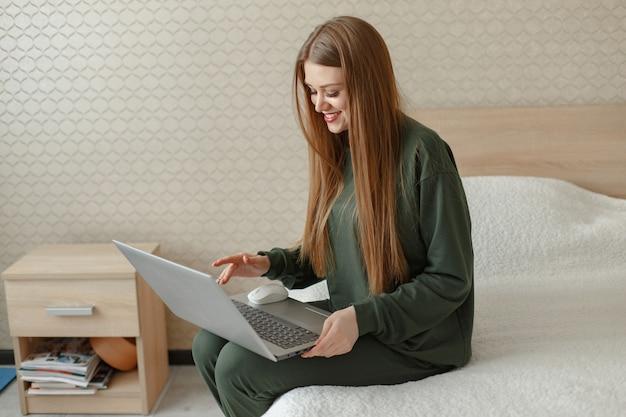 Femme, séance, lit, utilise, ordinateur portable
