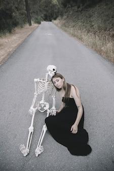 Femme, séance route, à, décoratif, squelette, de, homme