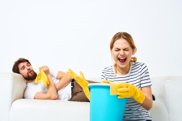 Femme avec un seau dans des gants en caoutchouc à la maison mari se trouve sur le nettoyage du canapé