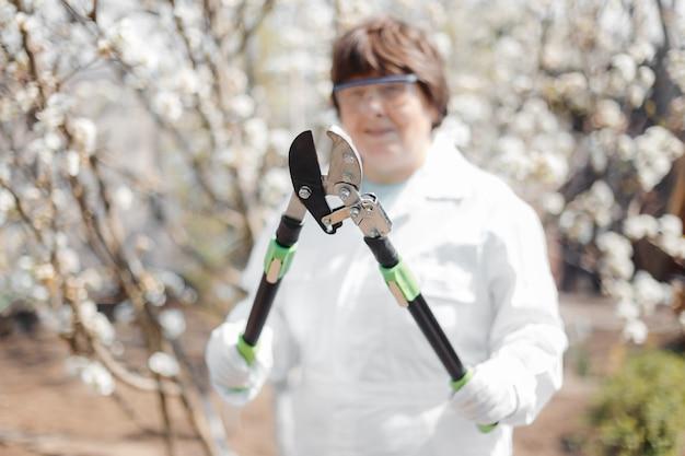 Une femme avec un sécateur dans ses mains dans le contexte d'un jardin fleuri au printemps. travaillez dans le jardin potager. élagage des arbres