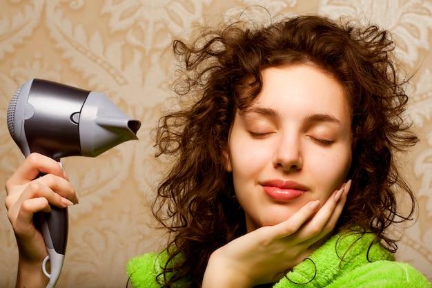 Femme séchant ses cheveux avec sèche-cheveux