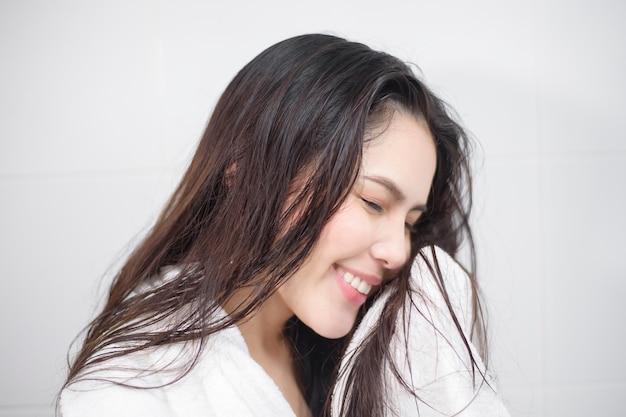 Une femme sèche ses cheveux avec une serviette après la douche