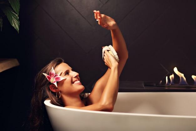 Femme séduisante adulte se détendre dans une baignoire avec cheminée en arrière-plan