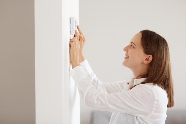 Femme séduisante à l'apparence agréable portant une chemise blanche de style décontracté, surveillant le système de chauffage de sécurité énergétique, contrôle numérique à la maison, thermostat tactile.