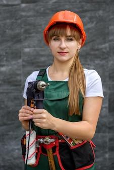 Femme séduisante en combinaison avec des perceuses en mains posant avec ceinture à outils