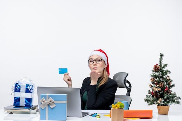 Femme séduisante confiante avec chapeau de père noël et portant des lunettes assis à une table et tenant une carte bancaire et envoyant un baiser au bureau
