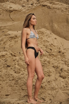 Femme séduisante coupe sexy en bikini relaxant bronzer seul à la plage de sable