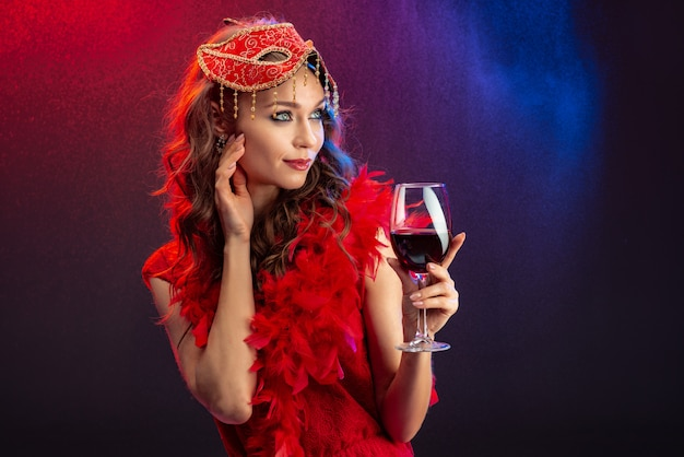 Femme séduisante dans un masque de carnaval rouge et boa avec un verre de vin levé à la recherche de suite