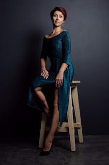 Une femme séduisante dans une robe de soirée pose sur un fond sombre.
