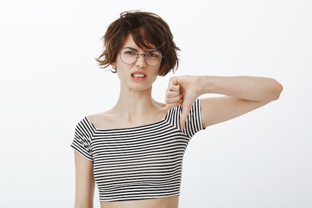 Femme séduisante déçu montrant le pouce vers le bas déçu, n'aime pas le geste
