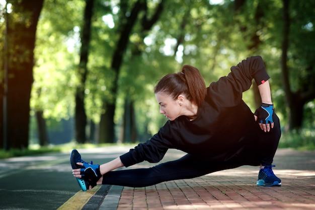 Femme séduisante et forte qui s'étend avant la remise en forme dans le parc d'été. concept sportif. mode de vie sain