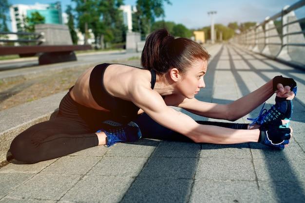Femme séduisante et forte qui s'étend avant la remise en forme sur le lac en été. concept sportif. mode de vie sain