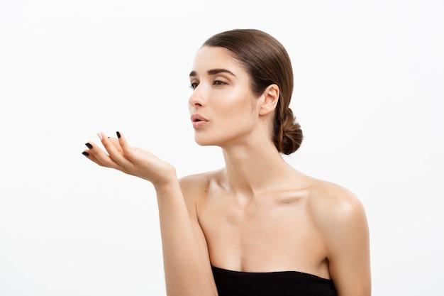 Femme séduisante jeune et en bonne santé, soufflant un baiser de son fond blanc de la main.