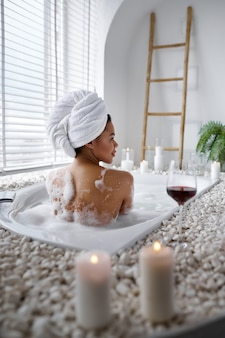 Femme séduisante se détendre dans un bain moussant, vue arrière. personne de sexe féminin dans la baignoire, soins de beauté et de santé au spa, traitement de bien-être dans la salle de bain, verre de vin, cailloux et bougies en arrière-plan