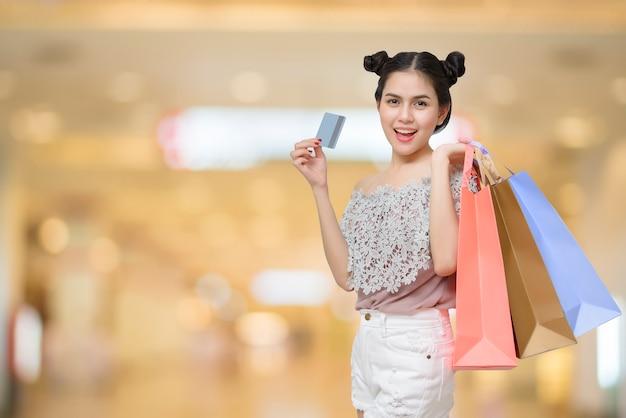 Femme séduisante shopper tenant des sacs à provisions avec carte de crédit