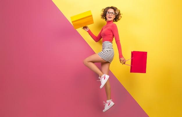 Femme séduisante souriante en tenue colorée élégante sautant avec des sacs à provisions