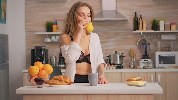 Femme séduisante en sous-vêtements sexy profitant du matin en buvant un verre de jus d'orange frais assis dans la cuisine. jeune femme avec des tatouages portant de la lingerie noire rafraîchissante dimanche matin