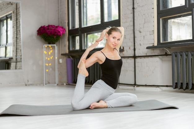 Femme séduisante sportive mince pratiquant le yoga, poses rajakapotasana, entraînement, portant des vêtements de sport, studio de yoga