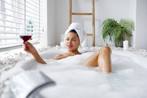 Une femme séduisante avec un verre de vin se détend dans un bain moussant. personne de sexe féminin dans la baignoire, soins de beauté et de santé au spa, traitement de bien-être dans la salle de bain, cailloux et bougies sur fond
