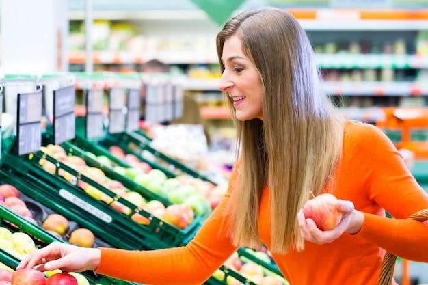 Femme sélectionnant des fruits au supermarché