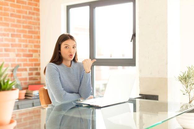 Femme semblant étonnée d'incrédulité, pointant un objet sur le côté et disant wow, incroyable