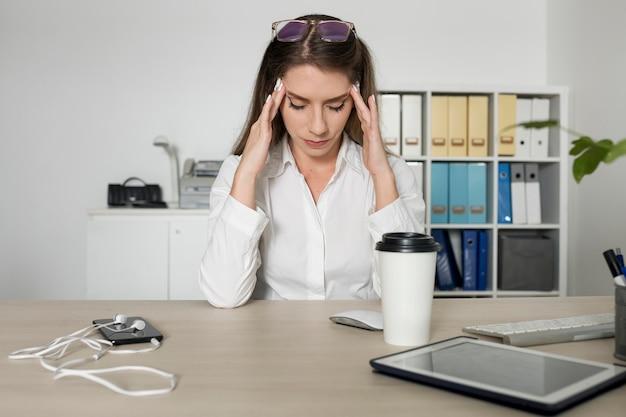 Femme semblant fatiguée au travail à cause de son temps passé au téléphone