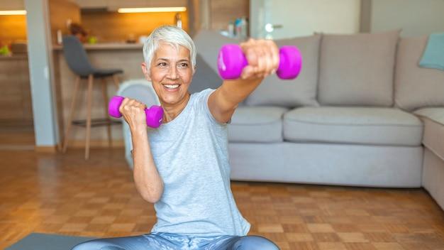 Femme senior active à la maison, l'exercice avec des poids. exercice de femme mûre à la maison.
