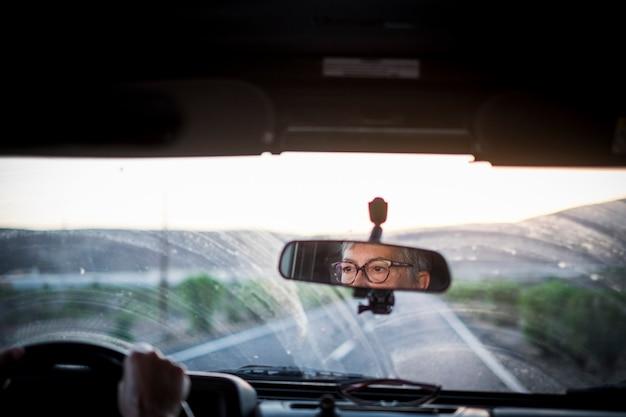 Femme senior adulte conduisant une voiture en regardant la route et utilisant des lunettes pour mieux voir