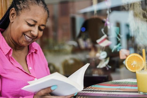 Femme senior africaine lisant un livre en plein air au bar restaurant - focus on face