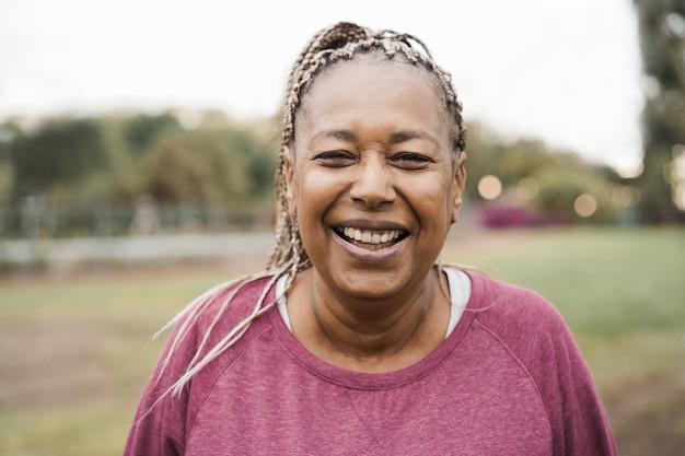Femme senior africaine souriant à la caméra en plein air dans le parc de la ville