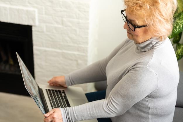 Femme senior âgée souriante avec ordinateur portable à la maison.